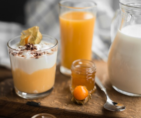 orenge: orange jam and cream mousse with physalis and carafe of milk, and classe of orange juice for breakfast