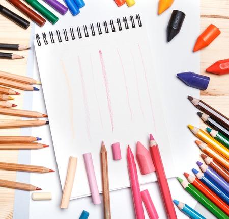 divers outils de dessin autour de portable blanc et rayures roses peintes sur une table en bois