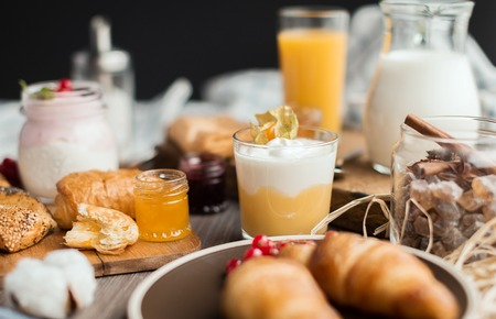 orenge: the cream mousse with a physalis and buns and croissants and jams on the wooden table Stock Photo