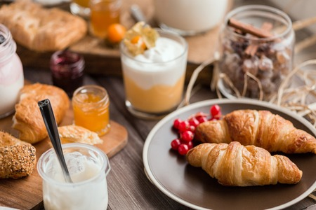 orenge: croissants with the red currant on the brown plate near cream mousse and other foor for breakfast