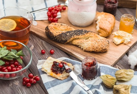 orenge: many cream mousses and jams on a wooden table near buns and croissants for breakfast Stock Photo
