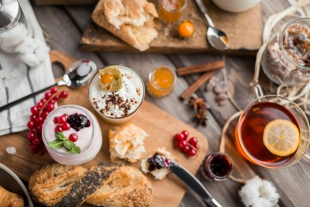 orenge: cream mousses and jams and buns and hot tea for a breakfast on a wooden table