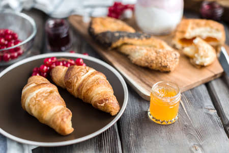 croissant with the red currant berries and the orange jam in the little jar Stok Fotoğraf