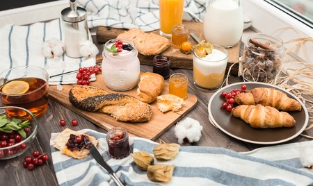 many cream mousses and jams on a wooden table near buns and croissants for breakfast Stok Fotoğraf