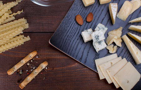 elegant appetizer with white wine different cheeses, bread and pasta on a wooden table