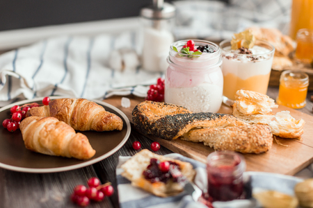 different cream mousses with berry and buns for breakfast on a wooden table Stok Fotoğraf