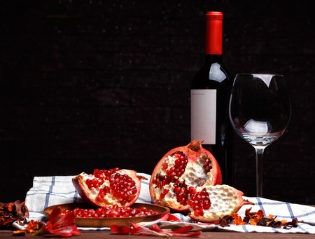 broken ripe pomegranate and red wine on a wooden table