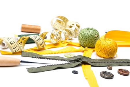 three plastic zipper, colorful skeins, various buttons, spiral measuring tape and a few reels of thread on a white background Stok Fotoğraf