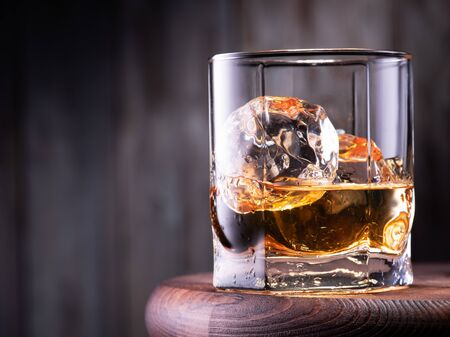 Glass of whiskey with ice cubes on the wooden table with wooden background