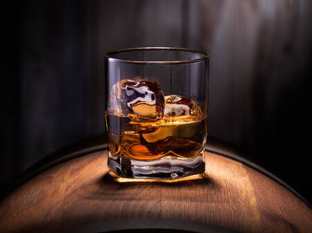Glass of whiskey with ice cubes on the wooden barrel with wooden background Stok Fotoğraf