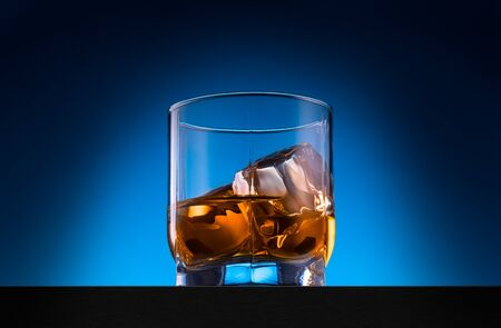 Glass of whiskey with ice cubes on the wooden table with blue background
