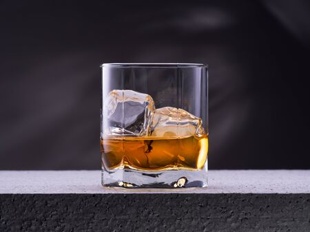 Glass of whiskey with ice cubes on the concrete table with gray background