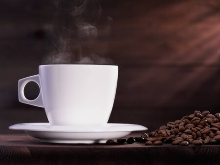 Coffee cup with steam and coffee beans on the wooden table Stok Fotoğraf