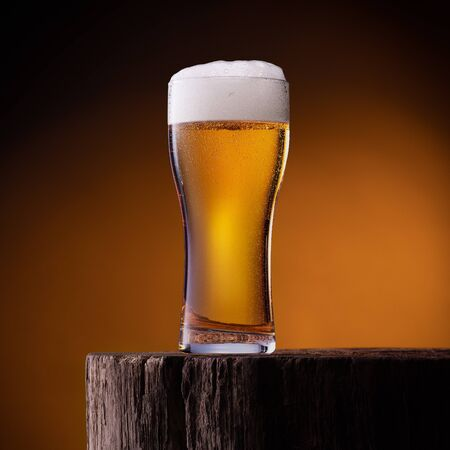 Glass of light beer on wooden table