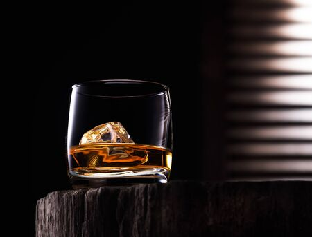 Glass of whiskey with ice cube on the wooden table with wooden background