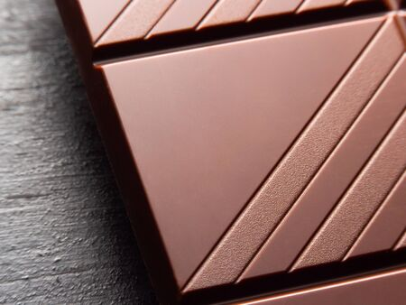 close up of a chocolate bar on black rustic background