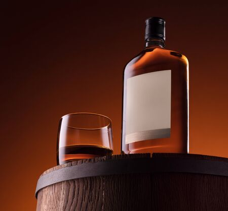 Glass and bottle of whiskey on the wooden barrel with orange background