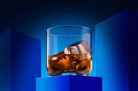 Glass of whiskey with ice cubes on small blue table with blue background