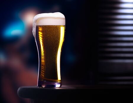 Glass of light beer on wooden table in cafe or restaurant with street view