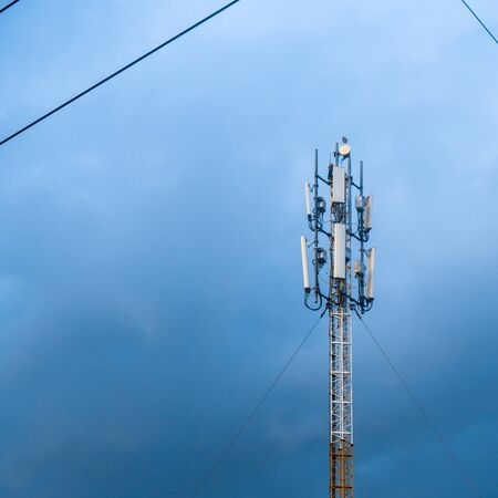 Technology of telecommunication GSM (5G,4G,3G) tower. Cellular phone antennas on a building roof. Receiving and transmitting stations with blue skies on the background. Stok Fotoğraf