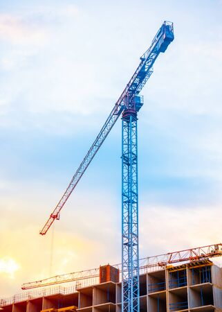Construction cranes on blue sky with sunset background. Imagens