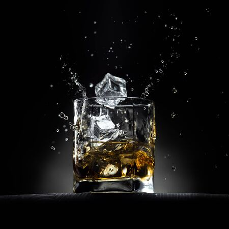 Glass of whiskey with ice cubes falling in it with splashes and drops. On the wooden table with dark background