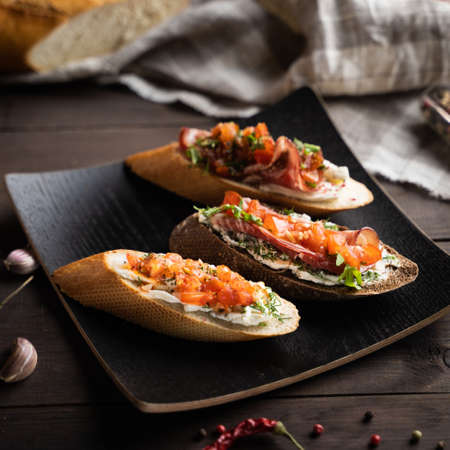 From above yummy bruschettas placed on square plate near napkin and spices in kitchen Stok Fotoğraf