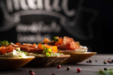 Row of delicious sandwiches placed near spices on wooden table in modern cafeteria Stok Fotoğraf