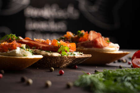 Closeup yummy bruschettas placed on table near spices and herbs with tomatoes in kitchen Stok Fotoğraf