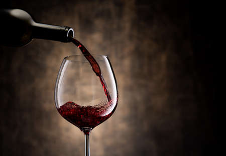 Trickle of fine red wine pouring from bottle into glass goblet against brown