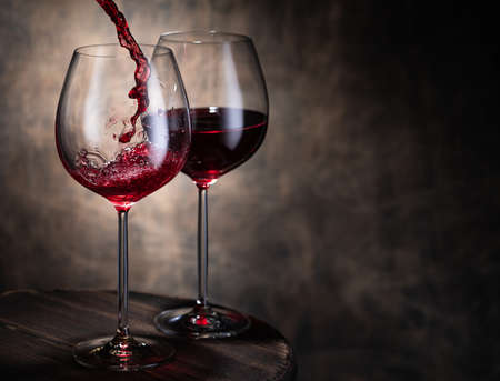 Trickle of fine red wine pouring from bottle into glass goblets against brown Stok Fotoğraf
