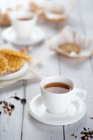 Cup of fresh herbal tea placed on wooden table near snacks for breakfast in morning