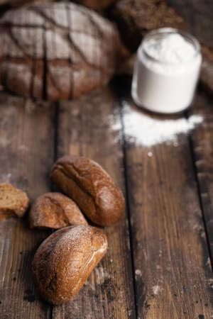 From above fresh rye buns placed on wooden table near loaf of bread and jar of flour in rustic kitchen Stok Fotoğraf