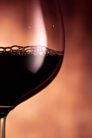 Closeup of clear transparent wineglass filled with red wine placed against blurred glowing red background