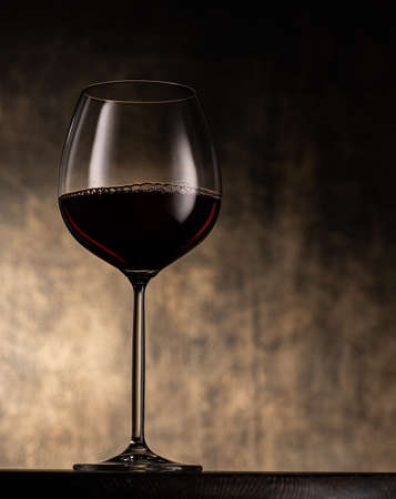 Elegant stemmed glass goblet filled with red wine placed on table against blurred shabby background Stok Fotoğraf