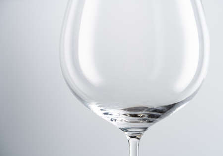 Closeup of empty transparent clean crystal goblet with slim stem placed against white background