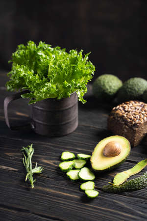 Fresh green vegetables and loaf of rye bread placed on wooden rustic table Stok Fotoğraf