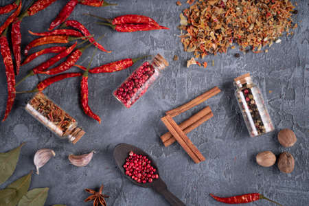 Top view of bunch of assorted fragrant spices placed on plaster surface in kitchen