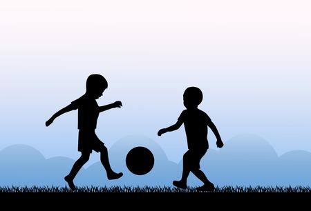 2 つの小さな男の子が草の上にボールを蹴る