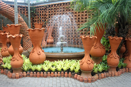 A fountain and pots in the Nong Nooch tropical botanic garden near Pattaya city in Thailand photo