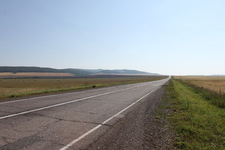 A dual high-way road without cars through fields with grass and crops K-05 between Achinsk and Ujur in Russia is going away far