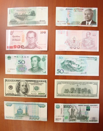 Cambodian riel by five thousands (5000), Thai baht by hundred (100), Chinese yuans by fifty (50), United states dollars by hundred (100)  and Russian rubles by one thousand (1000) denomination are on a table before a trip to Asia