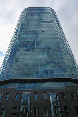 storied: A bottom view of the beautiful multi-storey mirrored building of Cobra Business Centre on the background of the gloomy cloudy sky in Novosibirsk city in Russia.