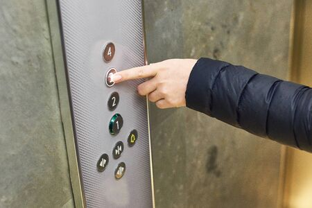 Woman hand press button of third floor in modern elevator, close-up.