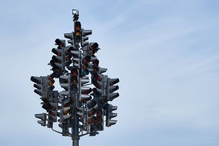 Art installation of many traffic lights located on single pole against blue sky. Space for text.