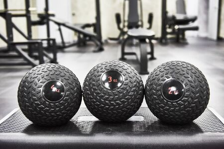 Three black filled weighted exercise balls in dense silicone cover with fluted surface inside Modern cross training Gym on stand close-up. Sport accessories.