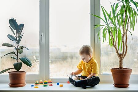 Child in yellow shirt sits on the windowsill at window with indoor plants, toys and looks at something on the screen of tablet computer.