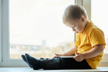 Child boy in yellow shirt sits on windowsill at the window and watches video cartoons on the screen of tablet computer.