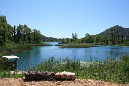 shallop: view on Bacinska lake in Croatia with small boat and tree stump