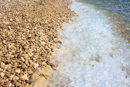 pebble beach: close up of a wave on a pebble beach